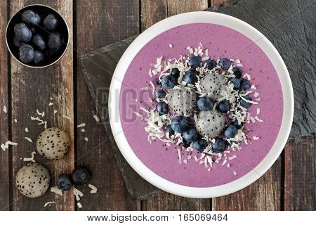 Smoothie Bowl With Blueberries, Dragon Fruit And Coconut, Overhead Scene On Rustic Wood