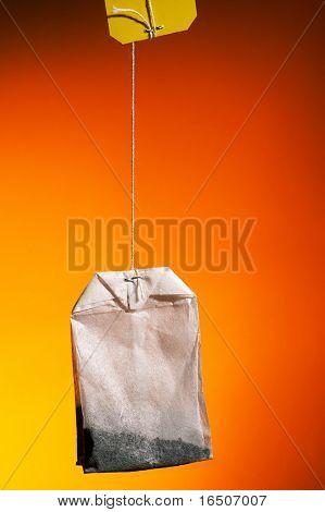 Tea bag on an dark orange background