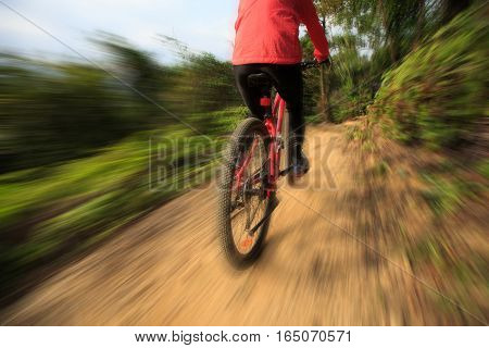 young woman riding bike on forest mountain trail