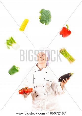Studio shot on white background of a cook juggling with vegetables
