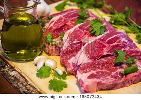 Raw meat. Raw beef steak on a cutting board made of wood with olive oil and garlic, Fresh meat.