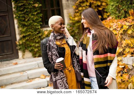 Young Multiethnic Women Listen Music At Autumn Day