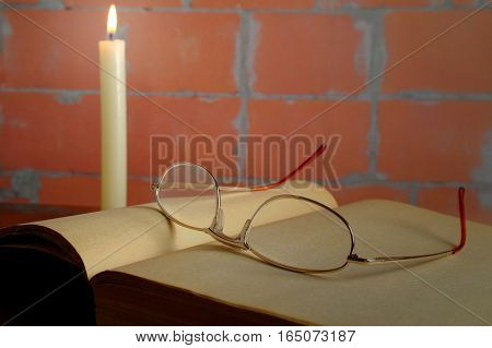 golden eyeglasses on an old opened faded book and burning candle