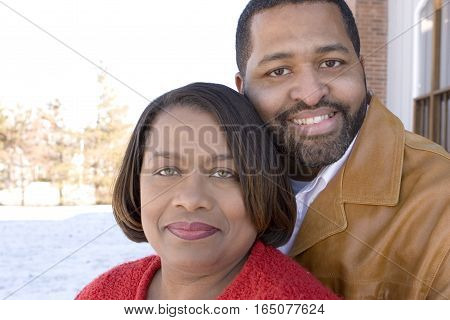 African American couple laughing and hugging in front of their home.