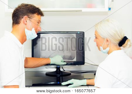 dentist and his assistant looking at dental x-ray