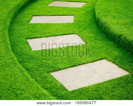Artificial green grass walk way with concrete plate background