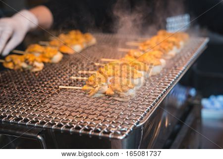 Scallop and sea eggs skewer grill with smoke japanese street food Tsukiji Fish Market Tokyo Japan