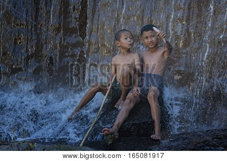 Children fishing at a stream near a waterfall and the boys are sleeping under the trees near the waterfall.