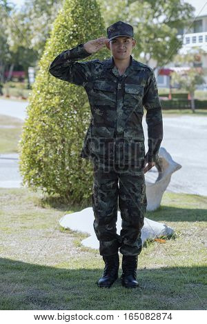 Soldier in green camouflage uniform saluting - Isolated.