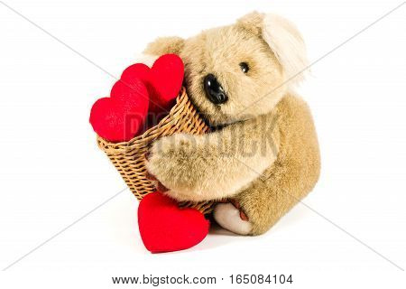 Cute teddy bear carrying bamboo basket full of red hearts for valentine' s day