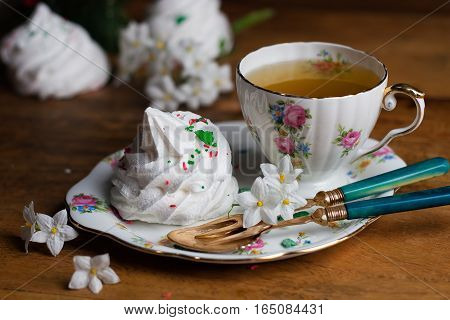 refined porcelain cup of tea and sauser with zephyr meringue marshmallow vintage fork and spoon wood flowers