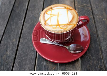 Hot caramel macchiato on wooden table  in the coffee shop