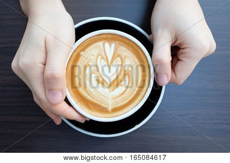 hands holding cup of coffee in coffee shop