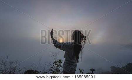 winter landscape with foggy hills at sunrisethe tourist standing on cliff in front of a sunset and taking pictures of fog in mountain view around.View of mountains winter landscape with foggy hills at sunrise.