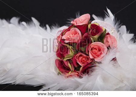selective focus with a bouquet of red roses shade on white feather beautiful Artificial flower sweet love on valentine or the anniversary day on black background has copy space