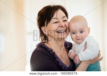 Senior woman hugging with her baby grandchild - interior scene