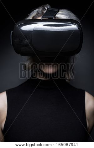 Woman wearing a futuristic looking virtual reality headset goggles. The device is technology that lets video gamers experience VR or AR augmented reality