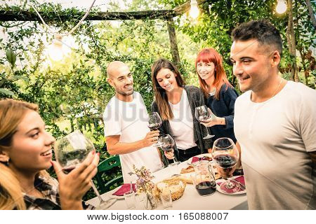 Happy friends having fun drinking red wine at backyard garden party - Youth and friendship concept together at farmhouse vineyard winery - Focus on background young people and bulb lights illumination