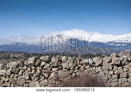 Stone wall. At the background, snow capped peaks of the Guadarrama Mountains. Photo taken in Colmenar Viejo Madrid Province Spain
