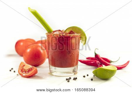 Bloody Mary cocktail with red hot chili peppers, slices of lime, celery sticks, a piece of tomato and copyspace