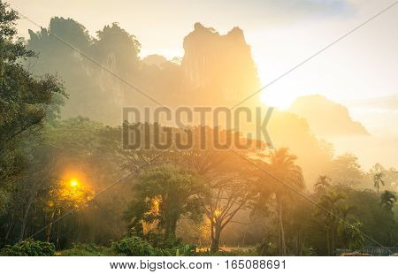 Thick wild vegetation and mountains in Khao Sok national park forest at sunset - Wanderlust travel lifestyle adventure around south east asian Thailand wonders - Enhanced sunflare halo with misty haze