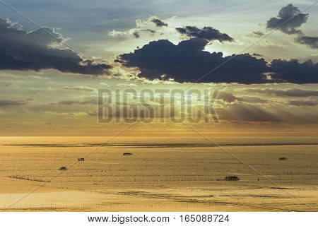 Shade of sunlight behind dark cloud before sunset over sea and shell farm