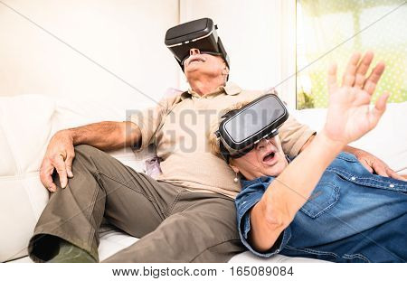 Senior couple having fun together with virtual reality headset - Retired people using new vr goggles glasses - New trends and technology concept - Focus on mature woman - Neutral apartment lights