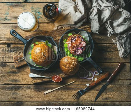 Homemade beef burgers with crispy bacon and fresh vegetables in small cast iron pans and glass of wheat beer on rustic board over old wooden background, top view, horizontal composition