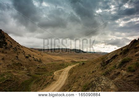 Storm clouds and the road stretches into the distance in the Caucasus mountains