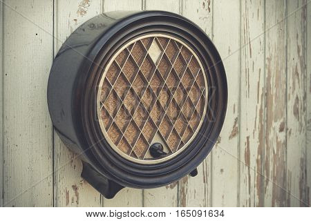 Old black radio hanging on a wooden wall