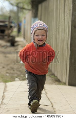 STINKA UKRAINE - APRIL 14 2016 - little dirty boy walks laughing with his tongue out on the street on April 14 2016 in Stinka village
