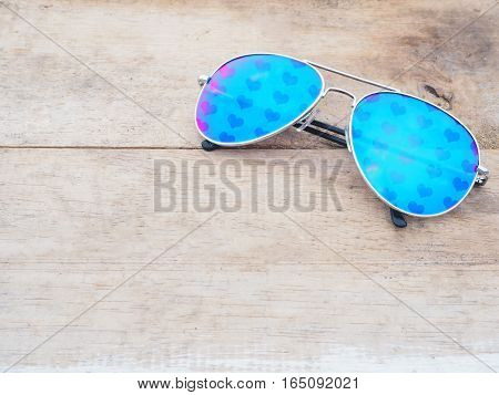 mirror glasses with heart shape pattern on wooden background. Love concept.