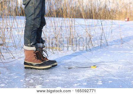 Ice fishing on frozen lake. Ice hole and winter rod.