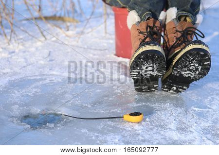 Ice fishing on frozen lake. Ice hole, winter rod and boots.