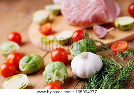 Vegetables and raw pork on cutting board