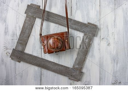 Old camera in a leather case hanging on white painted board