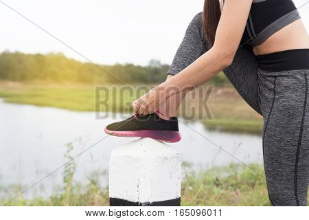 Woman Tying Shoe Laces. Female Sport Fitness Runner Getting Ready For Jogging Outdoors In Park