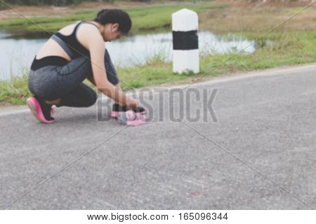 Woman Tying Shoe Laces. Female Sport Fitness Runner Getting Ready For Jogging Outdoors In Park (blur