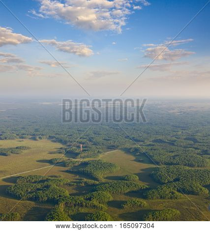 Aerial view over forest area with communications antenna tower in summer