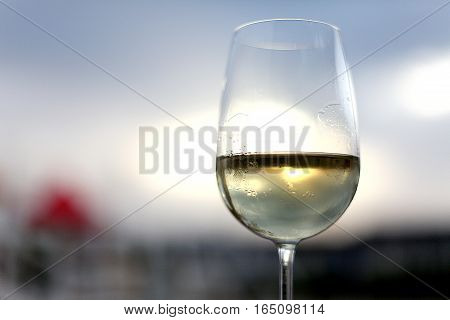 Glass of white wine on the sky background