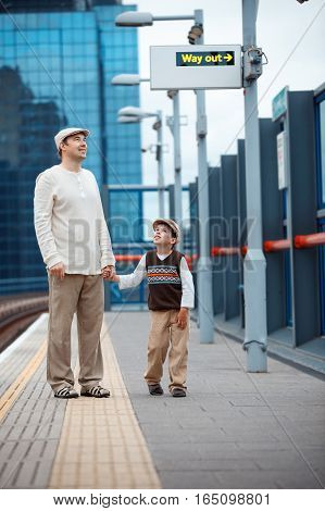 Young father and son waiting for train on railway station platform