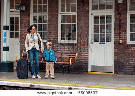 Young mother and son waiting for train on railway station platform