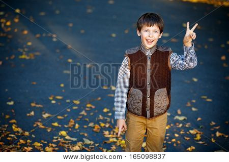 Admiring little boy laughing outdoors at beautiful autumn park