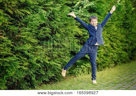 Cheerful little boy wearing in dark classic suit having fun outdoors. Children portrait. Stylish kid in suit