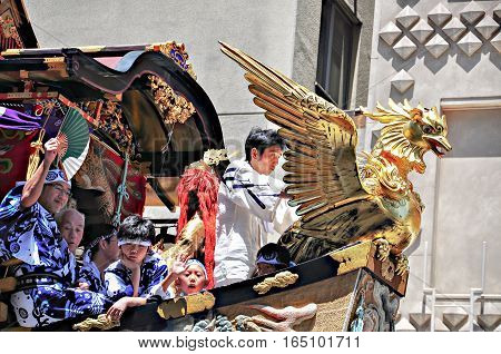 Kyoto Japan - July 17 2011: People riding on highly decorated float participating in Gion Festival Kyoto Japan