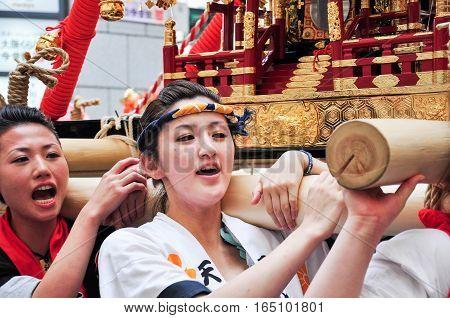 Osaka Japan - July 25 2012: Facial shot of unidentified young women worshipping the golden shrine in Tenjin Matsuri Osaka's biggest festival