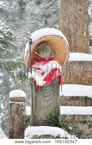 Jizo or stone statue wearing red apron under snow in Koyasan Japan poster