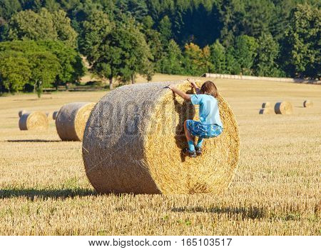 Boy Climbing a Bale of Hay on a Field in Summer