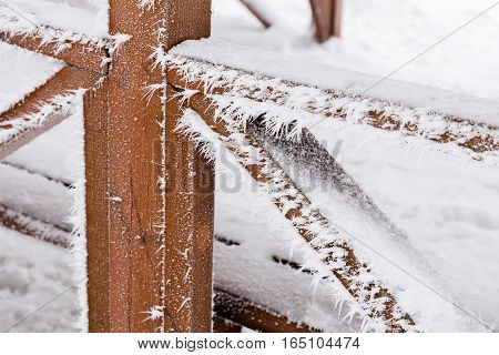 Hoarfrost in the form of long needles on a wooden handrail