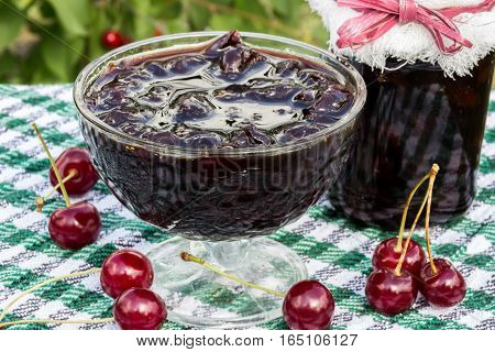 Glass bowl with cherry jam on a background of scattered cherries and cherry jam jar